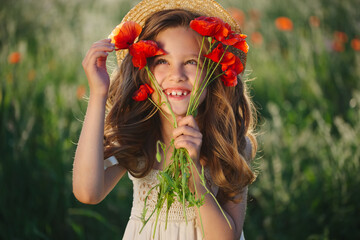 cute little girl in meadow with red poppies