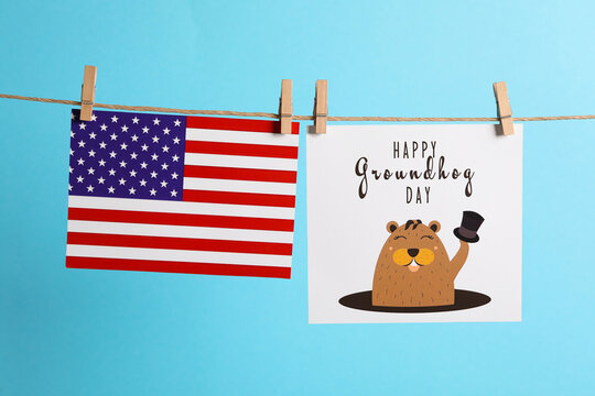 Happy Groundhog Day greeting card and American flag hanging on light blue background