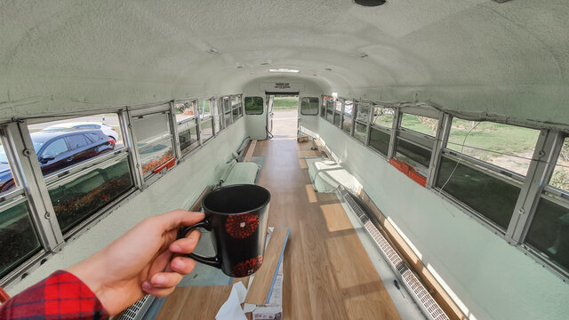POV shot of the photographer's hand holding a tea cup of coffee inside a bus in the process of being emptied, cleaned and renovated. New flooring.