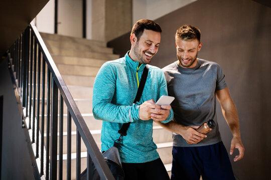 Handsome fit men friends talking, smiling after workout in gym