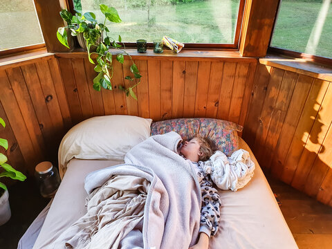 Shot from above of a young girl sound asleep in a mattress on the floor of a bungalow or veranda, half covered in blankets, in full daylight.