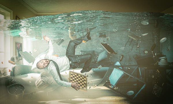 man in trouble in a flooded room of his home.