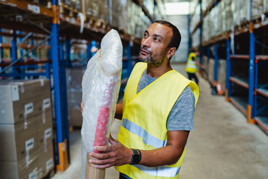 40 years old african american worker moving a package in a warehouse