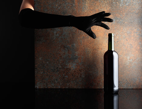 Woman hand in  glove reaches for a bottle of red wine.