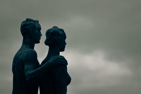 Statue Of Couple Against Cloudy Sky