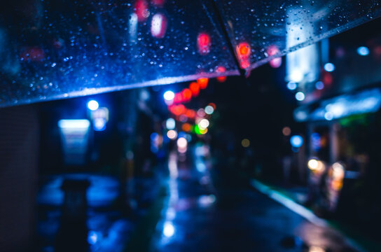 Defocused Image Of Wet Street At Night View From My Umbrella