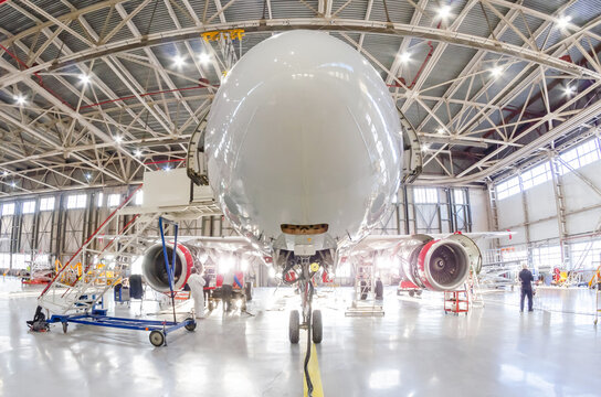 Aircraft in the under the hangar roof aviation industrial on maintenance, outside the gate bright light.
