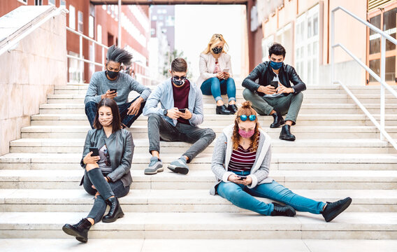 Urban milenial people using mobile phones covered by face mask on Covid third wave - Worried guys and girls watching video on smartphone - University students sitting at study break - Bright filter