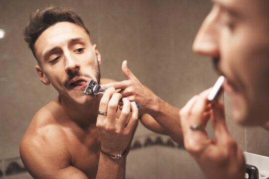 A man gesticulating in front of the mirror while shaving his beard