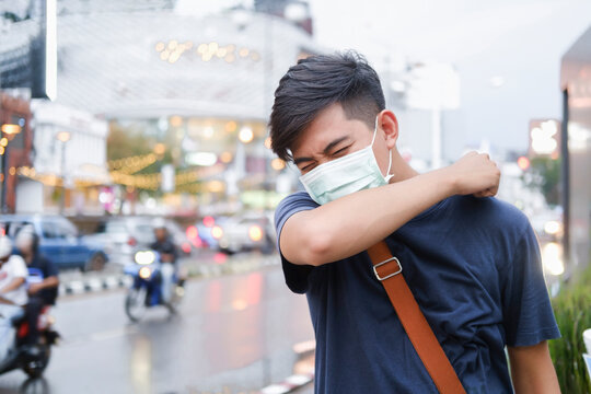 Close-up young man with protective face mask coughs in his elbow