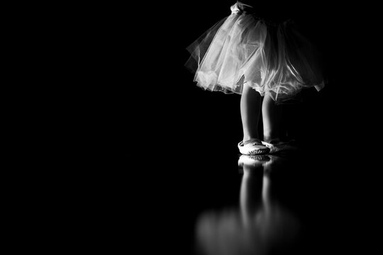 Little girl playing and dancing ballet in a tutu and ballet shoes
