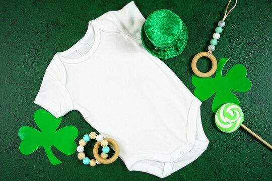 Happy St Patrick's Day baby wear onesie bodysuit, styled with leprechaun hat, shamrocks, on a textured green background. Mockup. Top view flat lay. Copy space.