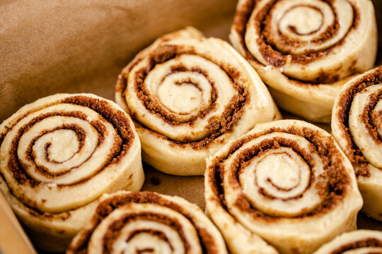 Raw cinnamon roll dough being prepared ready for baking