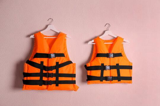 Orange life jackets on pink background. Personal flotation device