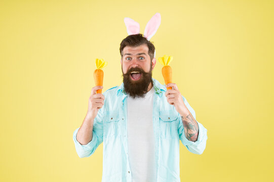Vitamin A for vision and health. Easter rabbit hold carrots. Bearded man choose vitamin vegetables. Eat right carbs. Spring vitamin deficiency. Vitamin food rich in beta-carotene
