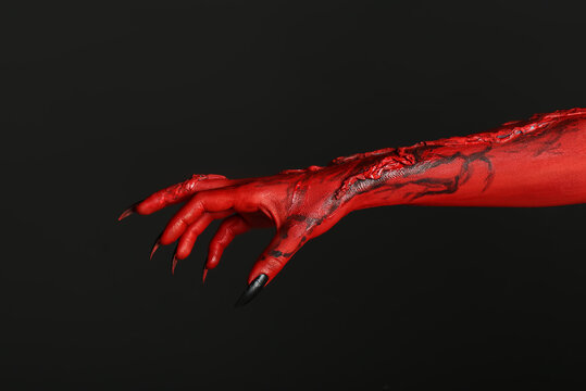 Scary monster on black background, closeup of hand. Halloween character