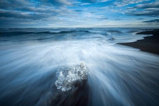 Chunk of ice on sea shore at Diamond beach near Jokulsarlon Glacier Lagoon, Iceland