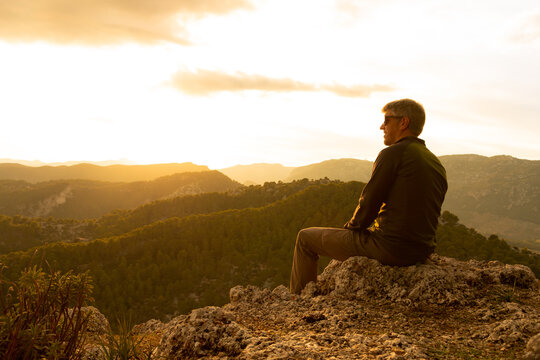 A man at sunset sitting on a rock looking at the mountains at sunset