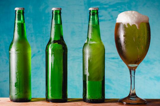 Tres botellas verdes con cerveza, un vaso de cerveza con espuma, sobre fondo azul.