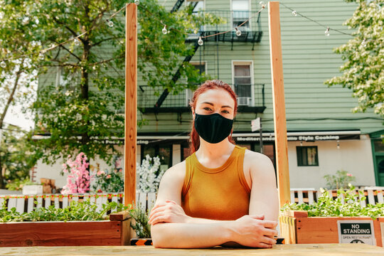 Young woman sitting in an outdoor restaurant table, wearing facemask.
