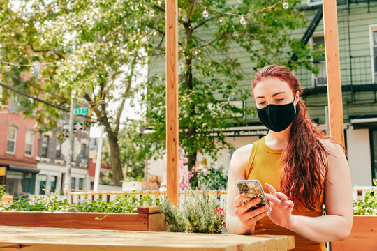 Young woman sitting in an outdoor restaurant table, wearing face mask.
