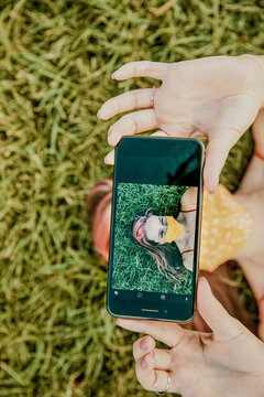 Young woman on grass taking selfie wearing face mask.