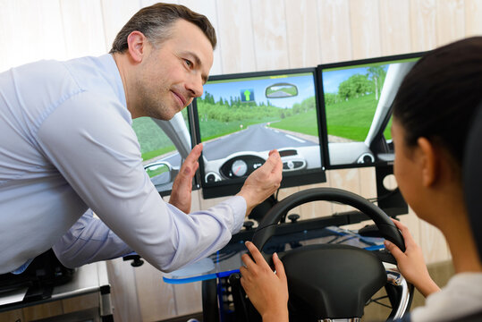 driving student being assisted in driving on a simulator