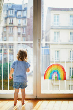 Adorable toddler girl looking through the window with rainbow drawing on it