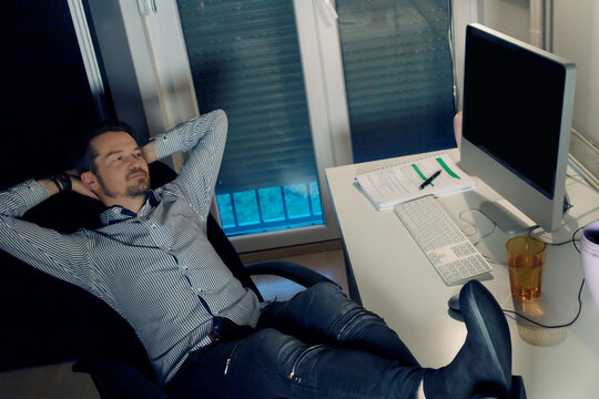 Relaxed businessman surfing the net on a computer at home office.