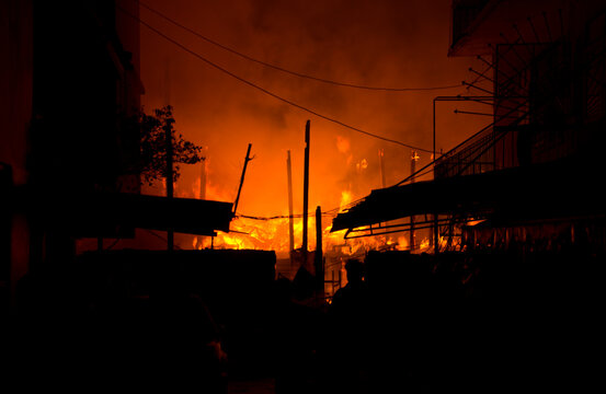 Houses, apartment, flat on fire and burning down at night in the market, slum, local center community, downtown in the big city. Asian cityscape location.