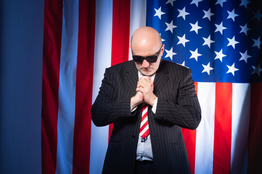 Man prays on background of American flag. He works as lobbyists America. Employee of a lobbying company USA. lobbying in United States of America. American lobbyist prays to god. Lobbying interests
