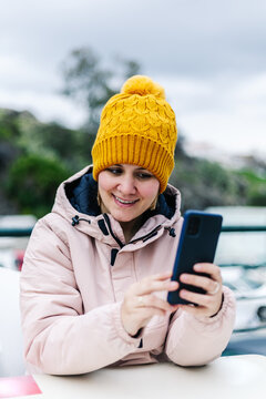 woman in winter clothes, smiling, looking at her cell phone, sitting on an outdoor terrace.