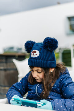 little girl playing handheld console, in blue winter clothes and woolen cap, outdoors