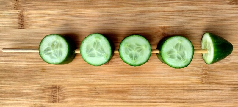 Cucumber Slices In Stick On Wooden Background