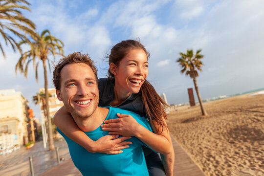 Happy couple in love Asian woman piggyback on smiling caucasian man - interracial lovers. Perfect dental smile models portrait in summer beach travel city lifestyle.