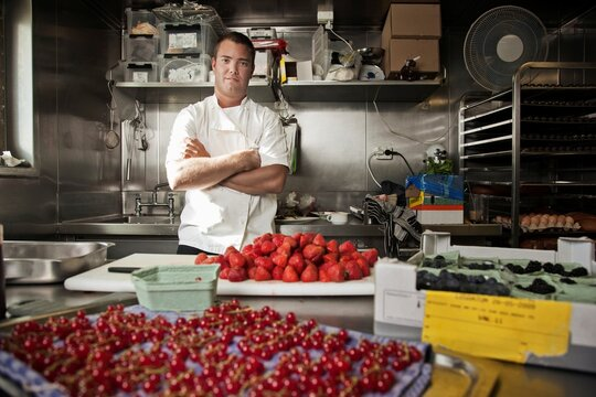 Pastry chef with his arms crossed standing in a kitchen with assorted berries being prepped on counter