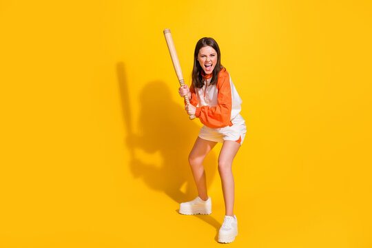 Full length photo portrait of crazy screaming girl holding baseball bat isolated on vivid yellow colored background