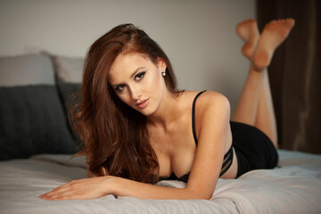 Fototapeta Boudoire photo of a gorgeus young woman lying in bed obraz
