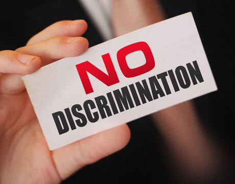 No discrimination words on a card in businessman hand. Social concept against racial and gender discrimination at work