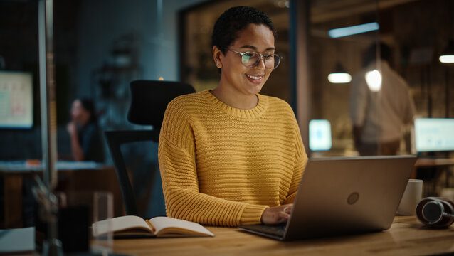 Young Hispanic Marketing Specialist Working on Laptop Computer in Busy Creative Office Environment in the Evening. Beautiful Diverse Multiethnic Female Project Manager Smiling.