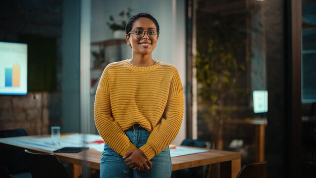 Portrait of a Young Latina with Short Dark Hair and Glasses Posing for Camera in Creative Office Environment. Beautiful Diverse Multiethnic Hispanic Female Wearing Yellow Jumper is Happy and Smiling.