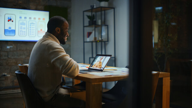 Handsome Black African American Project Manager is Making a Video Call on Laptop Computer in a Creative Office Environment. Male Specialist Talking to a Multiethnic Colleague Over a Live Camera.