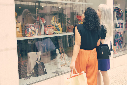 Female friends with shopping bags standing at store outside and staring at window with accessories. Low angle. Window shopping concept