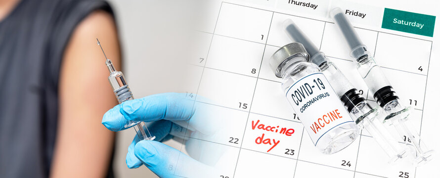 A doctor's hand holding a syringe and a calendar with the date of vaccination.