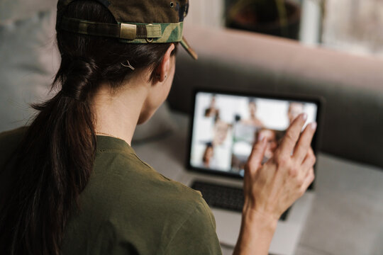 Soldier woman waving hand while making conference call on laptop