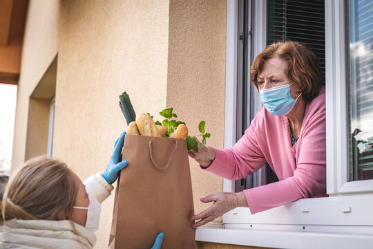Woman delivering groceries and food to her senior mother. Social distancing due coronavirus pandemic lockdown
