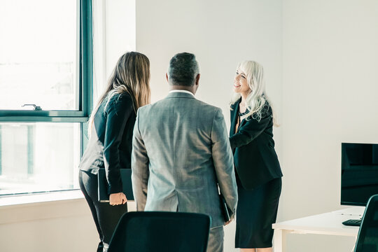 Confident grey-haired businesswoman greeting colleagues in office. Professional manager handshaking, smiling and meeting for discussion of project together. Business and communication concept