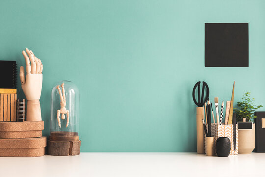 Creative desk with a blank picture frame, note, desk objects, drawing supplies, pencils, brushes, and plant near bright pastel wall. Artist workspace.