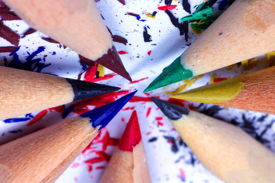 Top view of sharpened color pencil and shavings on white backgroun