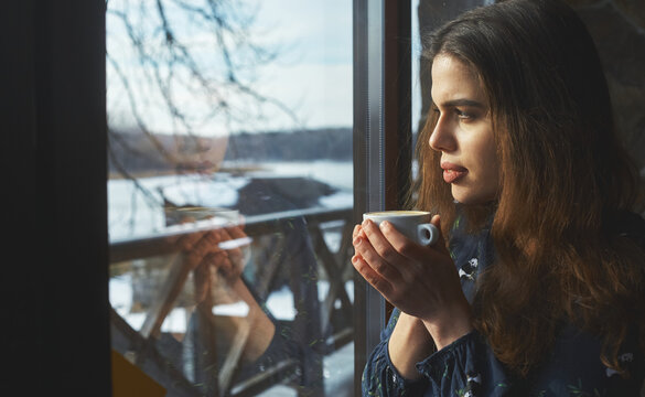 beautiful woman drinking coffee in the morning sitting by the window. view from outside.